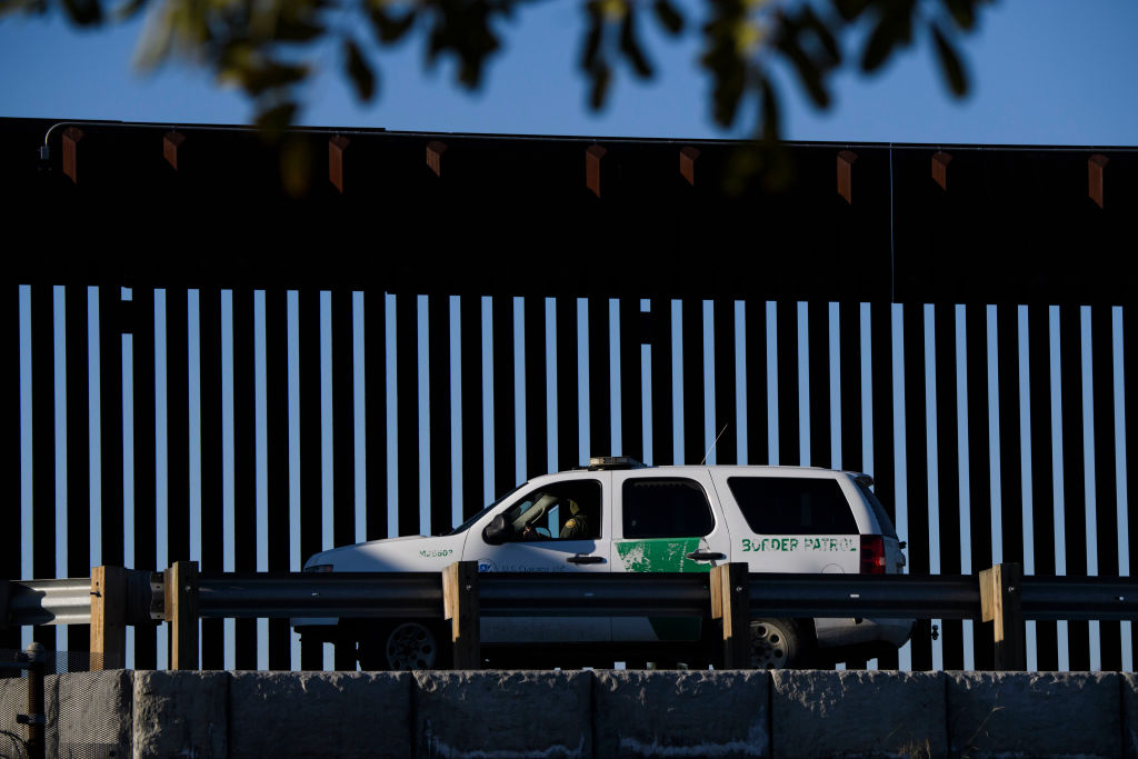 """A US Border Patrol agent sits in a vehicle along a border wall near the US Customs and Border Protection (CBP) San Ysidro Port of Entry at the US Mexico border on February 19, 2021 in San Diego, California. - The Biden administration plans to slowly allow 25,000 people with active cases seeking asylum into the US previously enrolled in the Migrant Protection Protocols program, known as """"Remain in Mexico,"""" with community organizations testing for Covid-19 and providing hotels to quarantine migrants upon arrival during the pandemic. (Photo by Patrick T. FALLON / AFP) (Photo by PATRICK T. FALLON/AFP via Getty Images)"""