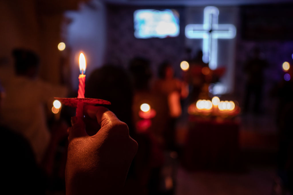 BANTEN, INDONESIA - DECEMBER 25: Christians hold candles during Christmas Eve mass at a church on December 25, 2018 in Carita, Banten province, Indonesia. At least 429 people have reportedly been killed after a volcano-triggered tsunami hit the coast around Indonesia's Sunda Strait on Saturday night, as 150 people remain missing and over 16,000 displaced. (Photo by Ulet Ifansasti/Getty Images)
