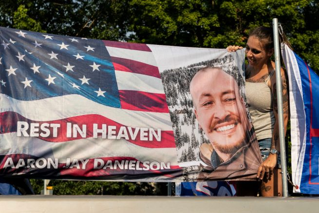 SALEM, OR - SEPTEMBER 07: Rebecca Thomas, a participant in a pro-Trump caravan rally, poses with a flag in memory of Aaron Jay Danielson, on September 7, 2020 in Salem, Oregon. Danielson was killed during another, recent pro-Trump caravan rally. Todays event, billed as the Oregon For Trump 2020 Labor Day Cruise Rally, began in Clackamas and made its way to the Oregon State Capitol in Salem. (Photo by David Ryder/Getty Images)