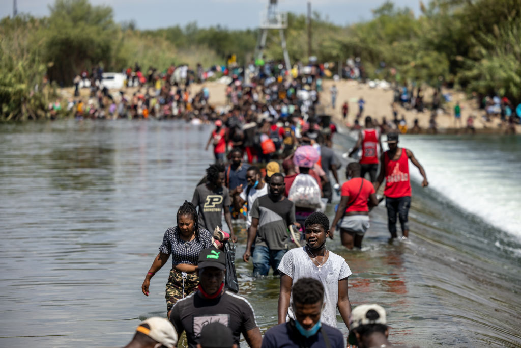 DEL RIO, TX - SEPTEMBER 18: Migrants cross the Rio Grande River near a temporary migrant camp under the international bridge on September 18, 2021 in Del Rio, Texas. The temporary migrant camp under the international bridge in Del Rio, TX has rapidly grown to more than 14,000 people and a lack of supplies has forced many migrants to cross the Rio Grande back into Mexico for basic necessities several times each day. (Photo by Jordan Vonderhaar/Getty Images)