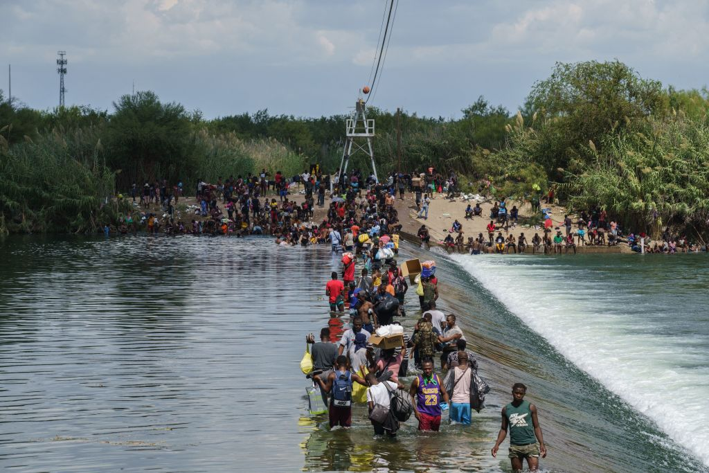 Migrants, many of them Haitian, cross the Rio Grande to get food and supplies near the Del Rio-Acuna Port of Entry in Ciudad Acuna, Coahuila state, Mexico on September 18, 2021. - The United States said on September 18 that it would ramp up deportation flights for thousands of migrants who flooded into the Texas border city of Del Rio, as authorities scramble to alleviate a burgeoning crisis for President Joe Biden's administration. The migrants who poured into the city, many of them Haitian, were being held in an area controlled by US Customs and Border Protection (CBP) beneath the Del Rio International Bridge, which carries traffic across the Rio Grande river into Mexico. (Photo by PAUL RATJE / AFP) (Photo by PAUL RATJE/AFP via Getty Images)