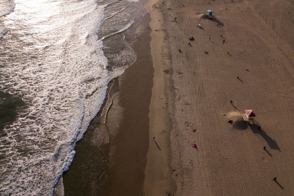 In this aerial image, people sit on the sand near the Huntington Beach pier before sunset on May 19, 2021 in Huntington Beach, California. - Orange County is now in the state's least-restrictive yellow tier of reopening. (Photo by Patrick T. FALLON / AFP) (Photo by PATRICK T. FALLON/AFP via Getty Images)