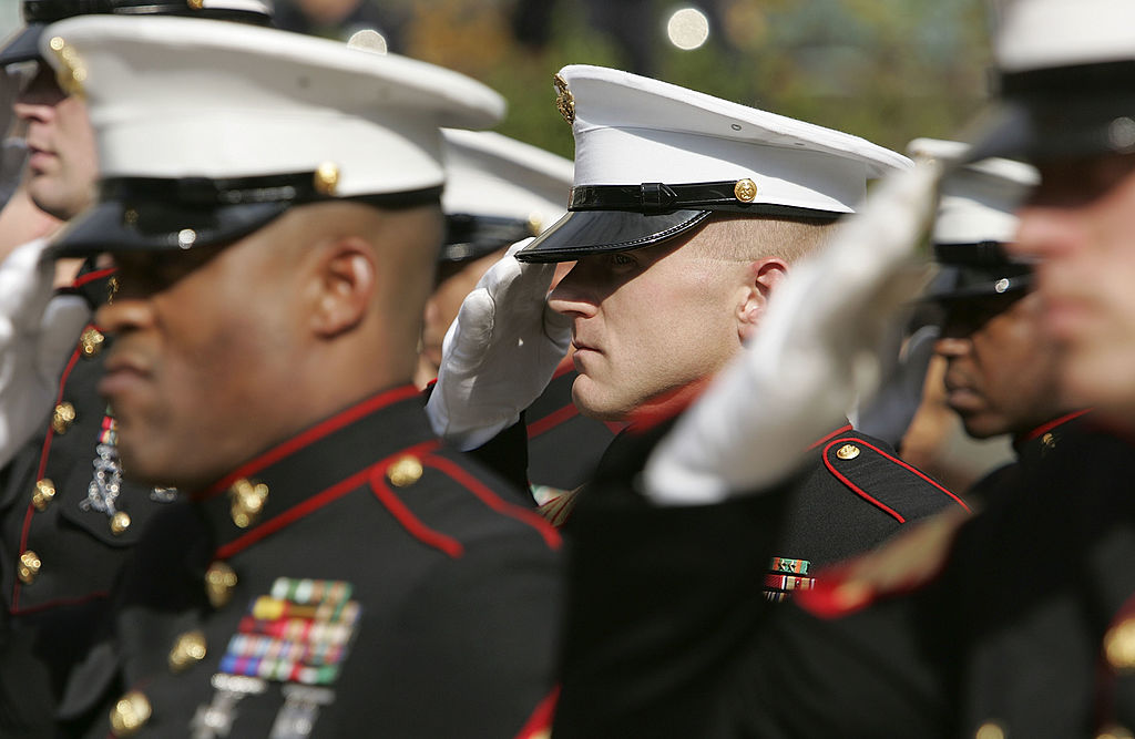 """SAN FRANCISCO - NOVEMBER 10: Members of the U.S. Marine Corp honor guard salute during the singing of the National Anthem during the unveiling ceremony for the new """"Distinguished Marines"""" commemorative stamps November 10, 2005 in San Francisco, California. The U.S. Postal Service issued a commemorative stamp series called """"Distinguished Marines."""" on the 230th birthday of the U.S. Marine Corp. The four-stamp series features images of U.S. Marines Lewis B. Puller, Daniel J. Daly, John Basilone and John A. Lejeune. (Photo by Justin Sullivan/Getty Images)"""