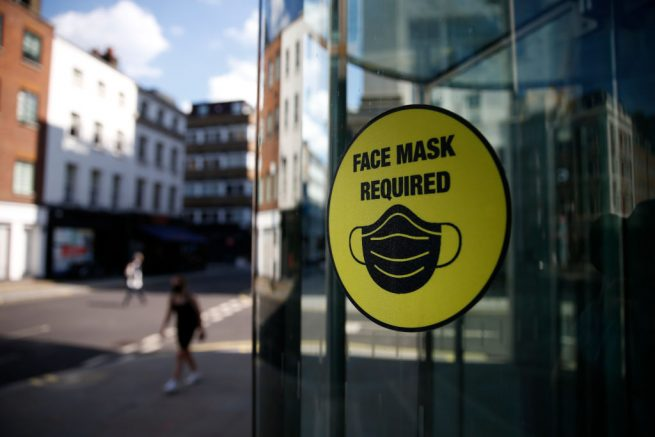 """LONDON, ENGLAND - JULY 18: A pedestrian walks past a sign saying """"Face Mask Required"""" on July 18, 2021 in London, England. On Monday, England will drop nearly all remaining pandemic-era social restrictions, such as those requiring distancing and size limits on gatherings. The move pits its vaccination programme against a more virulent Delta variant that has led to the UK's highest number of daily new infections since January. (Photo by Hollie Adams/Getty Images)"""