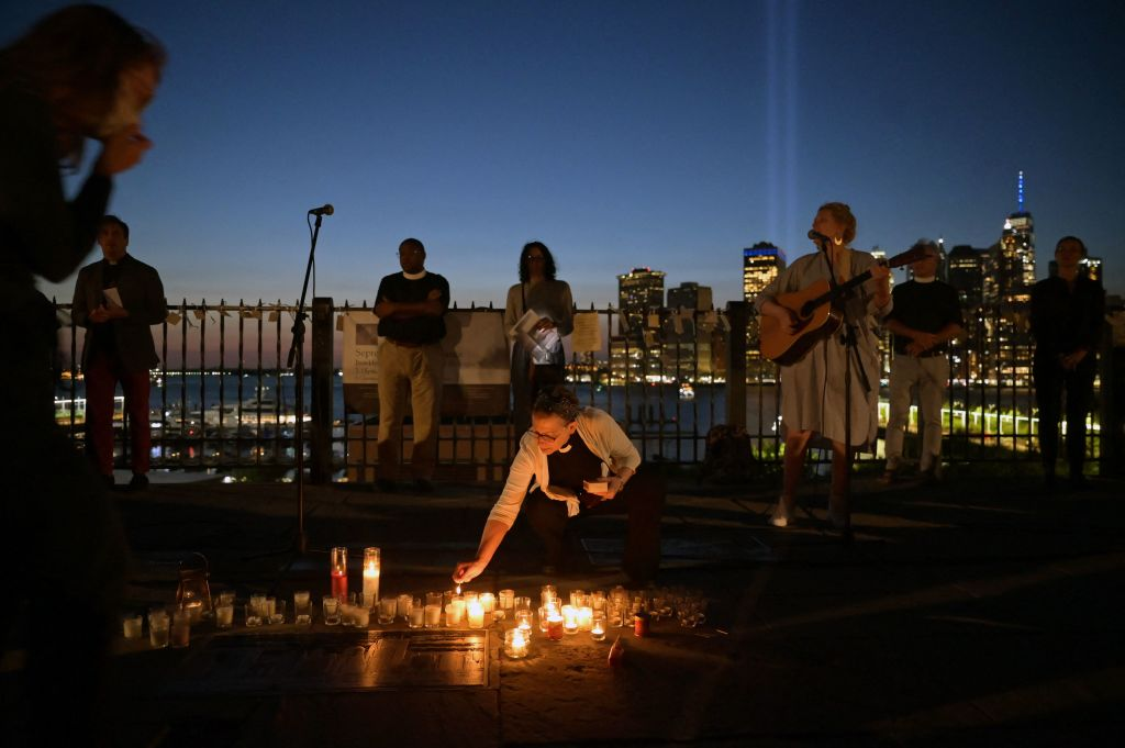 A woman lights a candle and another one plays the guitar during an interfaith vigil in Brooklyn Heights as the Tribute in Light is seen on the background as part of the commemoration for 20th anniversary of the terrorist attack in New York City on September 11, 2021. (Photo by Ed JONES / AFP) (Photo by ED JONES/AFP via Getty Images)
