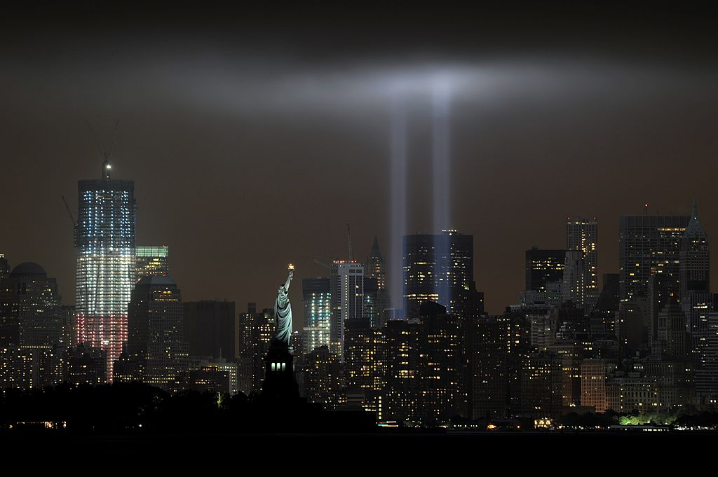 """The annual """"Tribute in Light"""" memorial echoing the twin towers of the World Trade Center illuminates the night sky during the 10th Anniversary of the September 11, 2001 attacks at the lower Manhattan site of the World Trade Center September 11, 2011, in this view from Bayonne, New Jersey. Also seen are the Statue of Liberty (C) and 1 World Trade Center (L). AFP PHOTO/Stan HONDA (Photo credit should read STAN HONDA/AFP via Getty Images)"""
