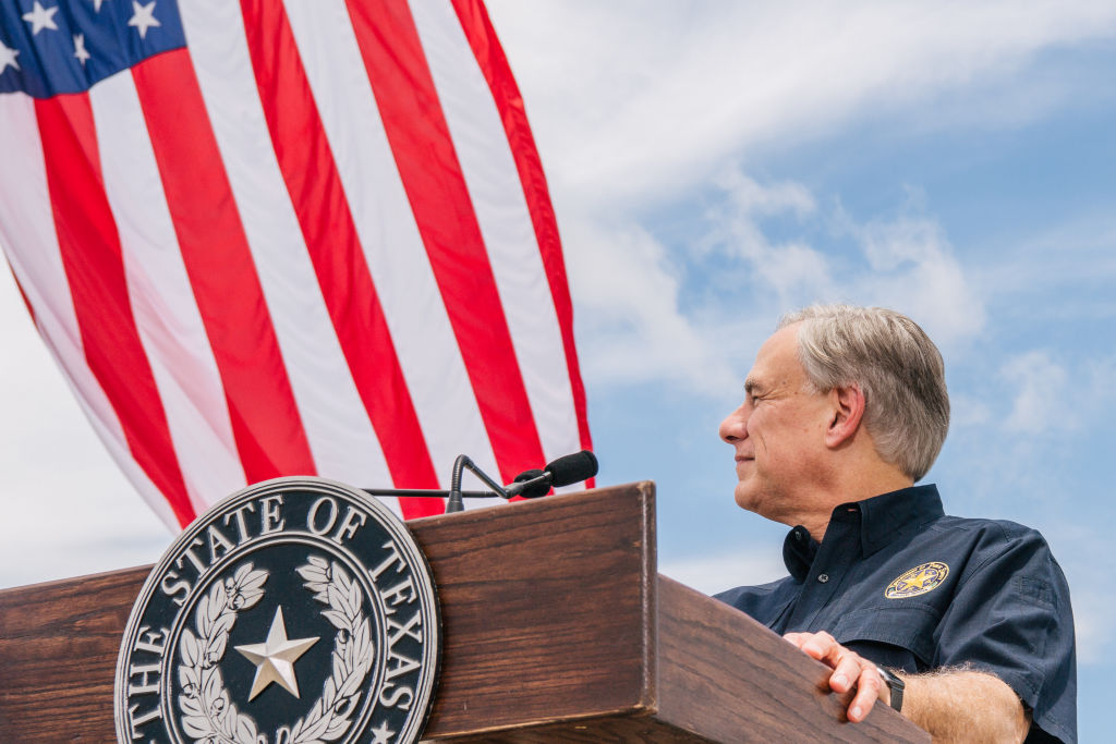 PHARR, TEXAS - JUNE 30: Texas Gov. Greg Abbott listens to former President Donald Trump's address during a tour to an unfinished section of the border wall on June 30, 2021 in Pharr, Texas. Gov. Abbott has pledged to build a state-funded border wall between Texas and Mexico as a surge of mostly Central American immigrants crossing into the United States has challenged U.S. immigration agencies. So far in 2021, U.S. Border Patrol agents have apprehended more than 900,000 immigrants crossing into the United States on the southern border. (Photo by Brandon Bell/Getty Images)