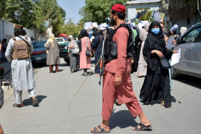 Taliban fighters keep vigil as Afghan women take part in an anti-Pakistan demonstration near the Pakistan embassy in Kabul on September 7, 2021. - The Taliban on September 7, 2021 fired shots into the air to disperse crowds who had gathered for an anti-Pakistan rally in the capital, the latest protest since the hardline Islamist movement swept to power last month. (Photo by Hoshang Hashimi / AFP) (Photo by HOSHANG HASHIMI/AFP via Getty Images)