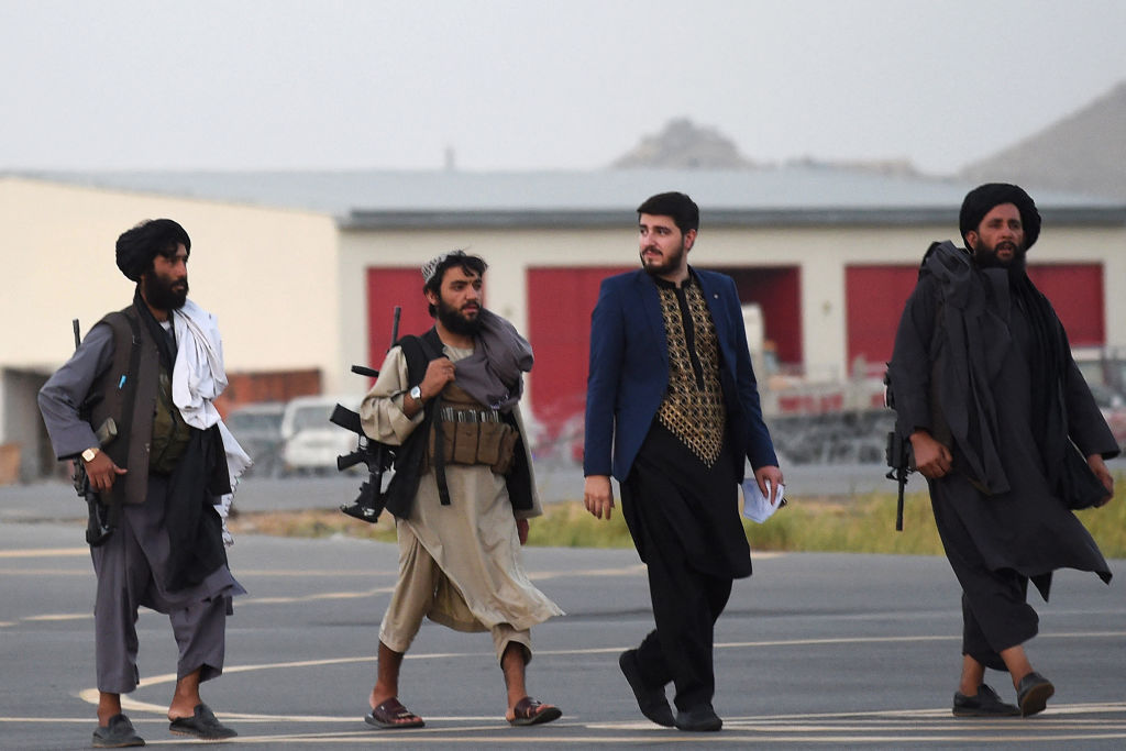 Taliban fighters walk through the tarmac after a Qatar Airways aircraft took off from the airport in Kabul on September 9, 2021. - Some 200 passengers, including US citizens, left Kabul airport on September 9, 2021, on the first flight carrying foreigners out of the Afghan capital since a US-led evacuation ended on August 30. (Photo by WAKIL KOHSAR / AFP) (Photo by WAKIL KOHSAR/AFP via Getty Images)