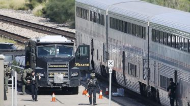 A Tucson Police Department SWAT truck is parked near the last two cars of an Amtrak train in downtown Tucson, Ariz., Monday, Oct. 4, 2021. One person is in custody after someone opened fire Monday aboard an Amtrak train in Tucson, Arizona, police said. The shooting happened just after 8 a.m. on a train parked at the station in the city's downtown. Authorities say the scene has been secured and no threat remains. (Mamta Popat/Arizona Daily Star via AP)