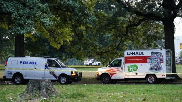 Police vehicles and a U-Haul truck are shown at a crime scene in Philadelphia, Monday, Oct. 4, 2021. Police in Philadelphia say a nurse fatally shot his co-worker at a hospital, fled the scene and was shot in a gunfight with police that wounded two officers. After the shooting, the gunman left the hospital in a U-Haul box truck. A short time later, four officers were alerted to the suspect's location by a passerby near a school. (AP Photo/Matt Rourke)
