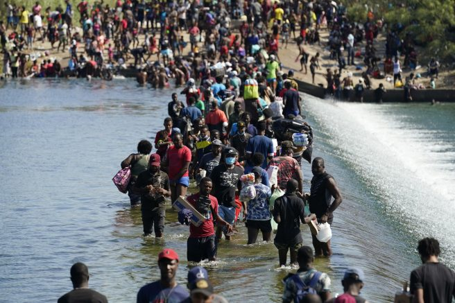 Haitian migrants use a dam to cross to and from the United States from Mexico, Friday, Sept. 17, 2021, in Del Rio, Texas. (AP Photo/Eric Gay)