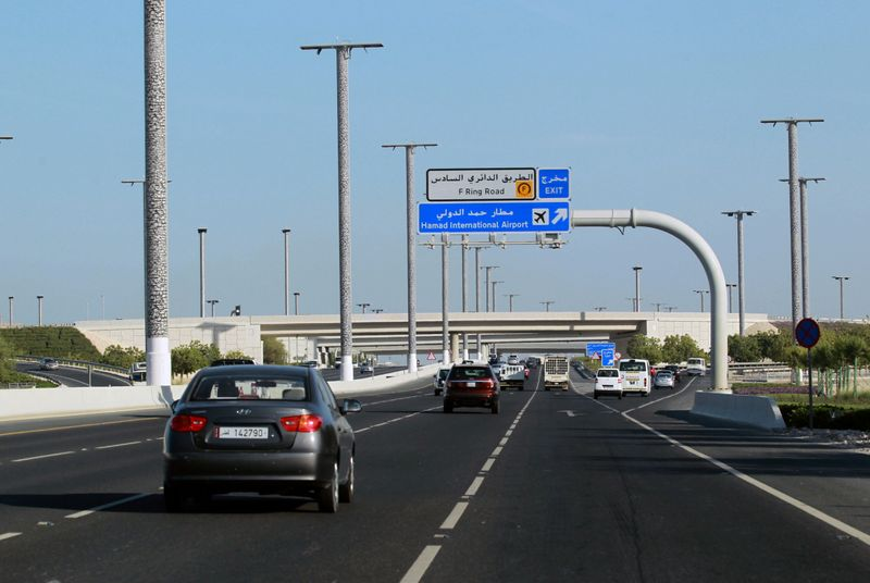 Cars drive on road leading to Hamad International Airport in Doha