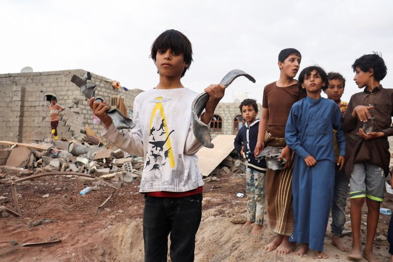 A boy holds shrapnel of a missile at the site of Houthi missile attack in Marib