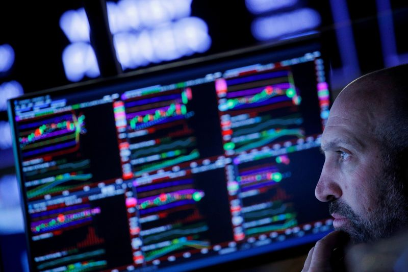 FILE PHOTO: Traders work on the floor of the New York Stock Exchange (NYSE) in New York City