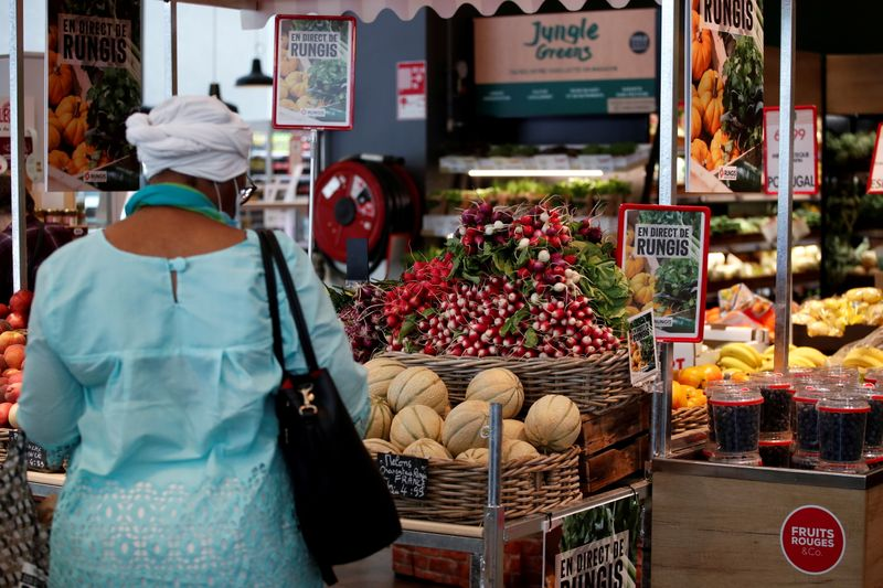 FILE PHOTO: A customer shops for vegetables at a Monoprix supermarket operated by Casino Group, in Paris