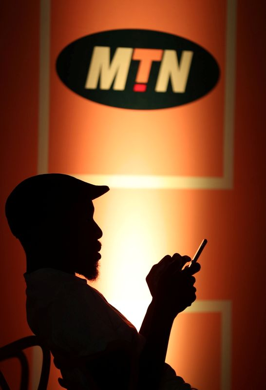FILE PHOTO: Guest types on his mobile phone as he sits below an MTN logo during the launch of its mobile money service in Johannesburg