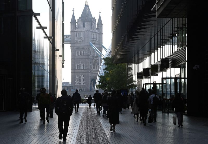 FILE PHOTO: Workers walk towards Tower Bridge during the morning rush hour in London