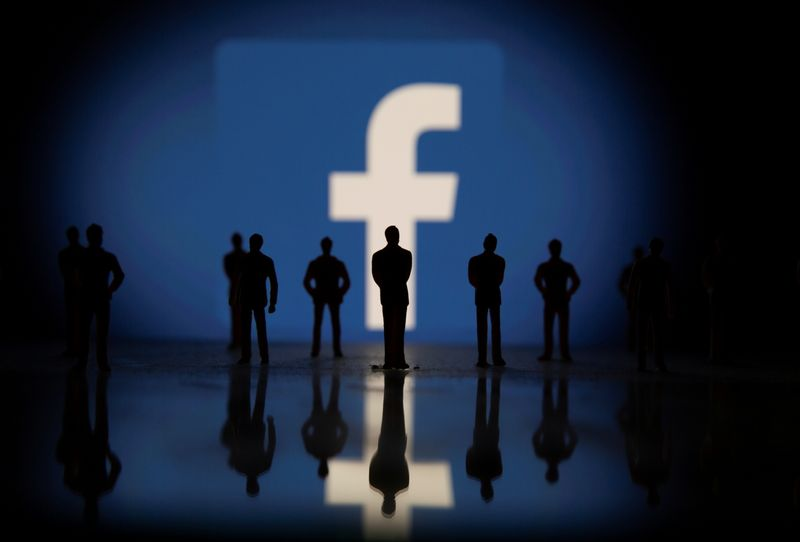 Small toy figures are seen in front of displayed Facebook logo in this illustration