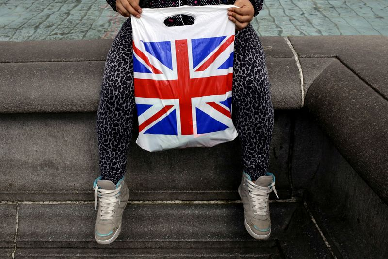 A woman holds a Union Flag shopping bag in London