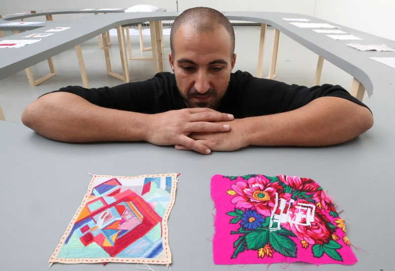 Palestinian artist Majd Abdel Hamid poses for Reuters during his exhibition in Brussels