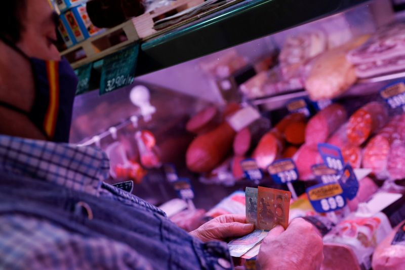 FILE PHOTO: A man wearing a face mask shops at a market in Madrid