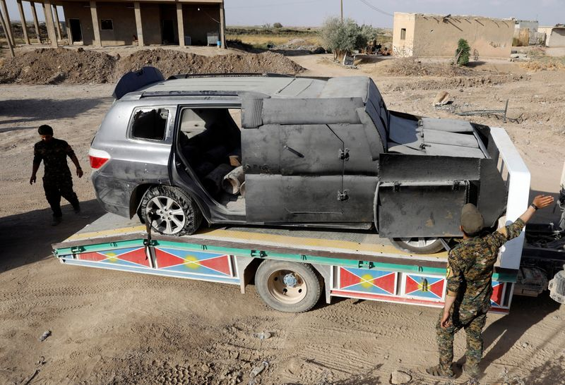 Members of Syrian Democratic Forces transport a suicide car bomb used by the Islamic State militants in Raqqa