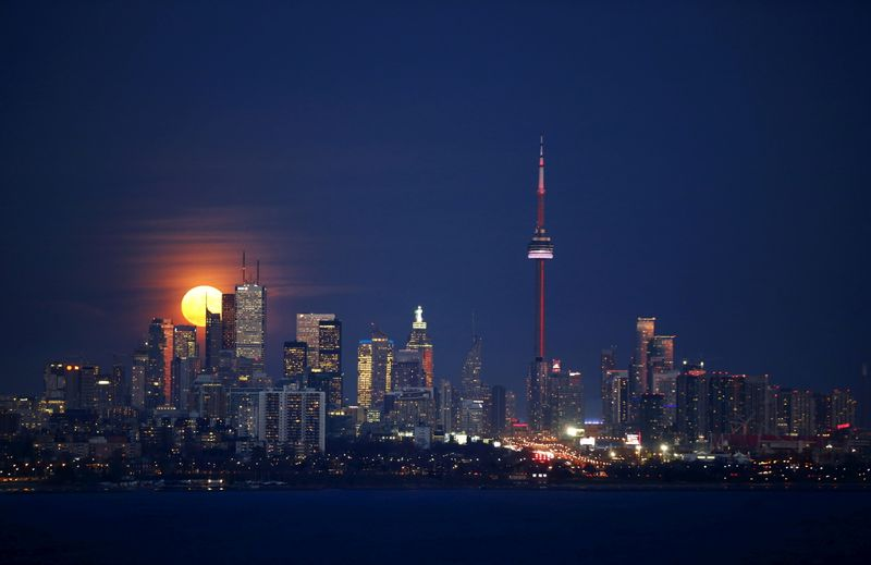 FILE PHOTO: The moon rises behind the skyline and financial district in Toronto