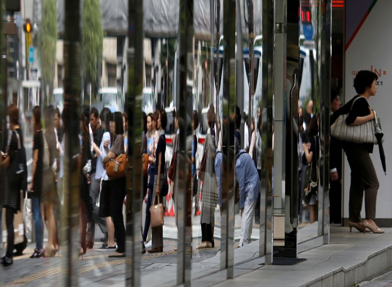FILE PHOTO: People are reflected in the windows of a dapartment store in a shopping district in Tokyo