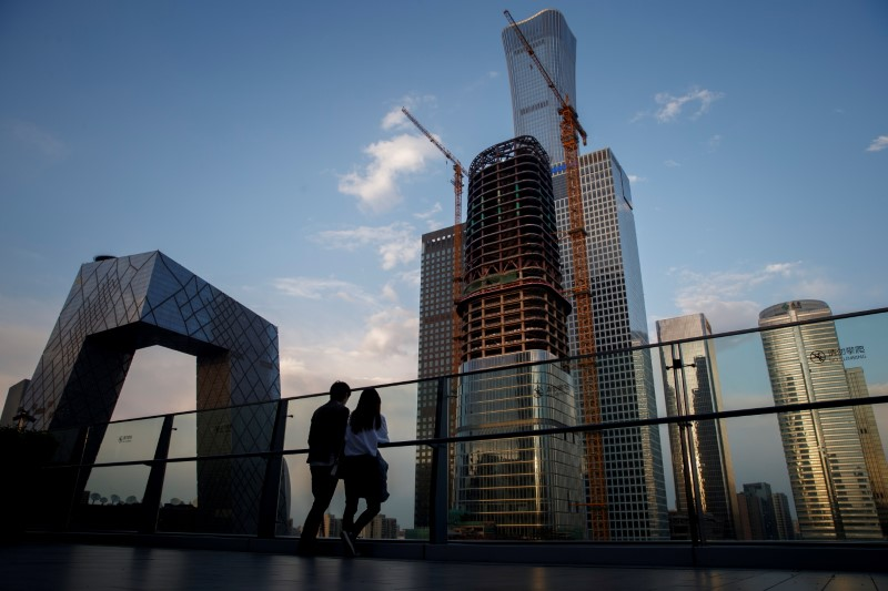 FILE PHOTO: People look at the skyline of the Central Business District in Beijing