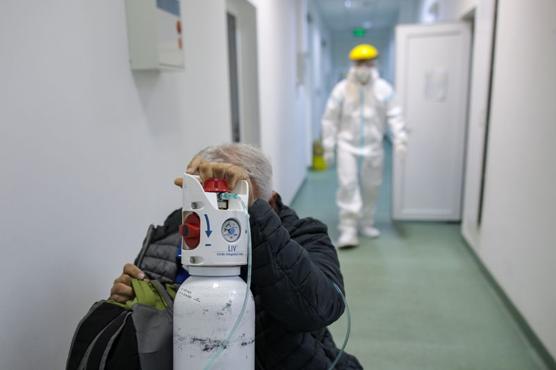 FILE PHOTO: A man sits in a wheel chair while taking in oxygen from a mobile tank and waiting to be placed on an extra bed in the COVID-19 ward of Marius Nasta Pneumology Institute