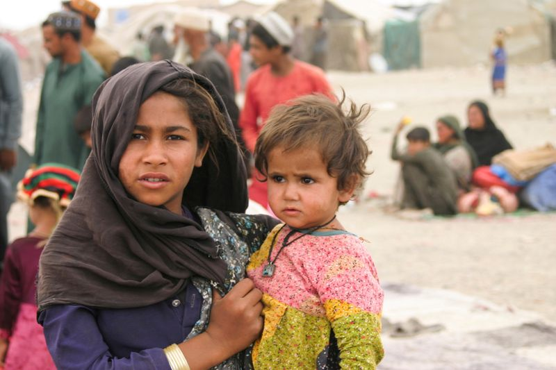 FILE PHOTO: Siblings who arrived from Afghanistan with their families are seen at their makeshift tents as they take refuge near a railway station in Chaman