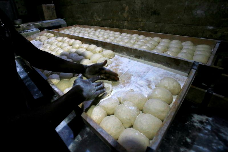 FILE PHOTO: A worker prepares bread dough before baking in a traditional oven at a bakery in Khartoum