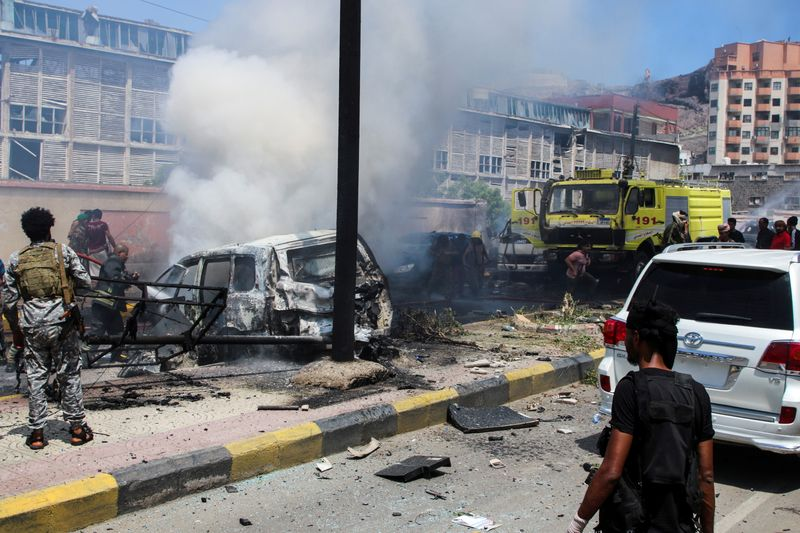 Policemen and firefighters work at the scene of a blast in Aden