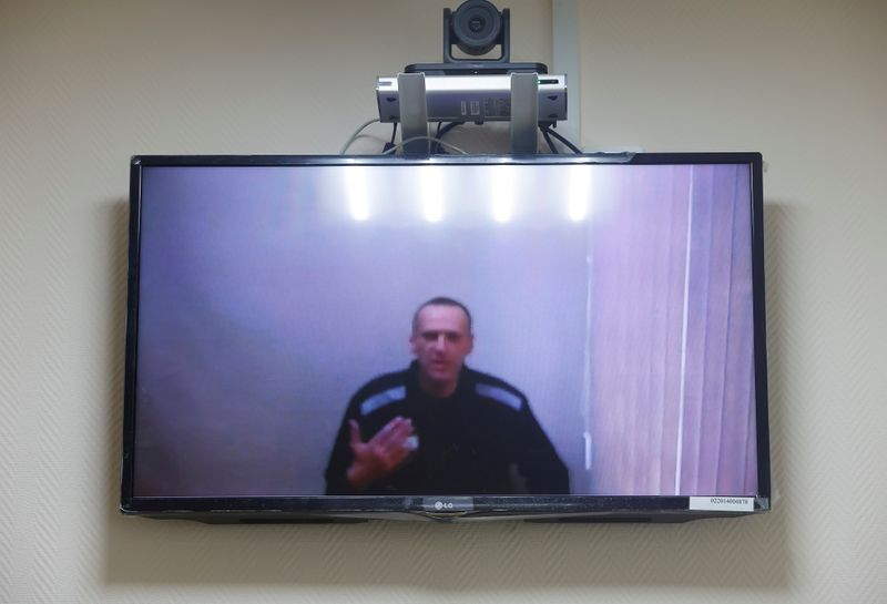 FILE PHOTO: Russian opposition leader Alexei Navalny is seen on a screen via a video link during a hearing in Petushki