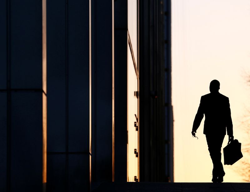 FILE PHOTO: A worker arrives at his office in the Canary Wharf business district in London