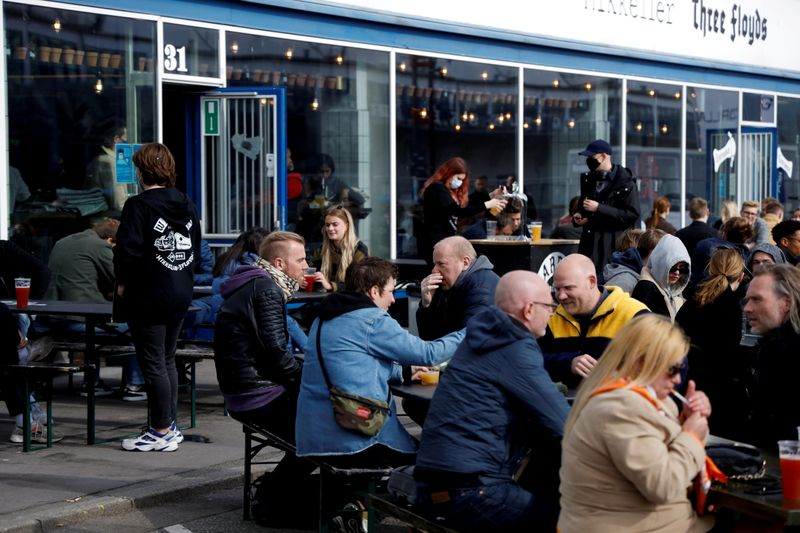 FILE PHOTO: Customers sit outside a bar after COVID-19 lockdown partial lift, in Copenhagen