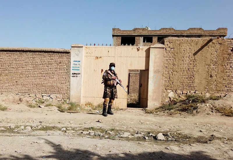 A Taliban solider stands guard in front of a house neighbouring the Islamic State hideout raided by Taliban forces on Sunday night in northern Kabul