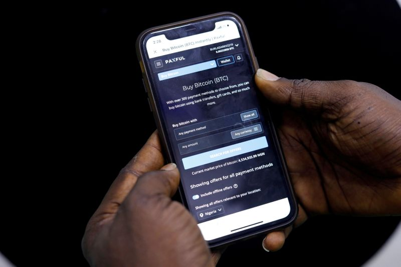 FILE PHOTO: Abolaji Odunjo, a gadget vendor who trades with bitcoin, demonstrates a bitcoin application on his mobile phone in Lagos