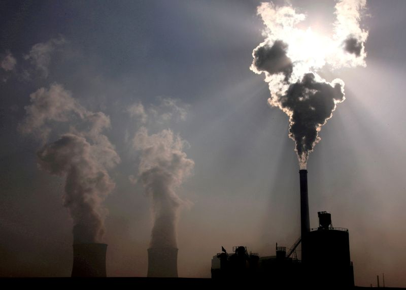FILE PHOTO: A coal-burning power plant can be seen behind a factory in the city of Baotou, in China's Inner Mongolia Autonomous Region