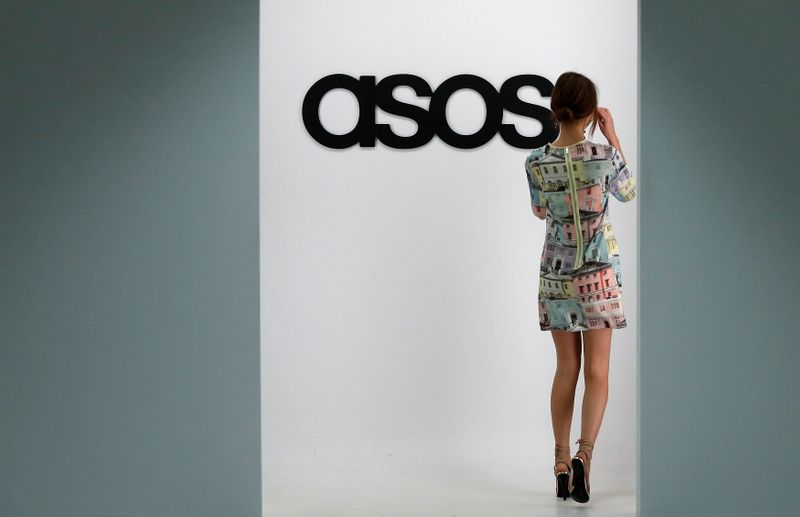 FILE PHOTO: A model walks on an in-house catwalk at the ASOS headquarters in London, Britain