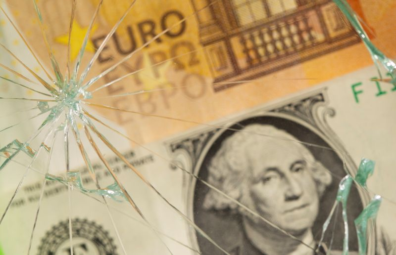 U.S. dollar and euro banknotes are seen through broken glass in this illustration