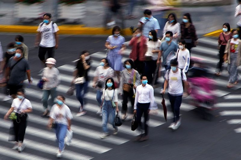FILE PHOTO: People wearing face masks walk on a street in Shanghai