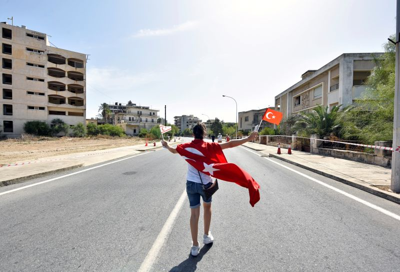 A woman walks while holding Turkish and Turkish Cypriot flags in the abandoned coastal area of Varosha