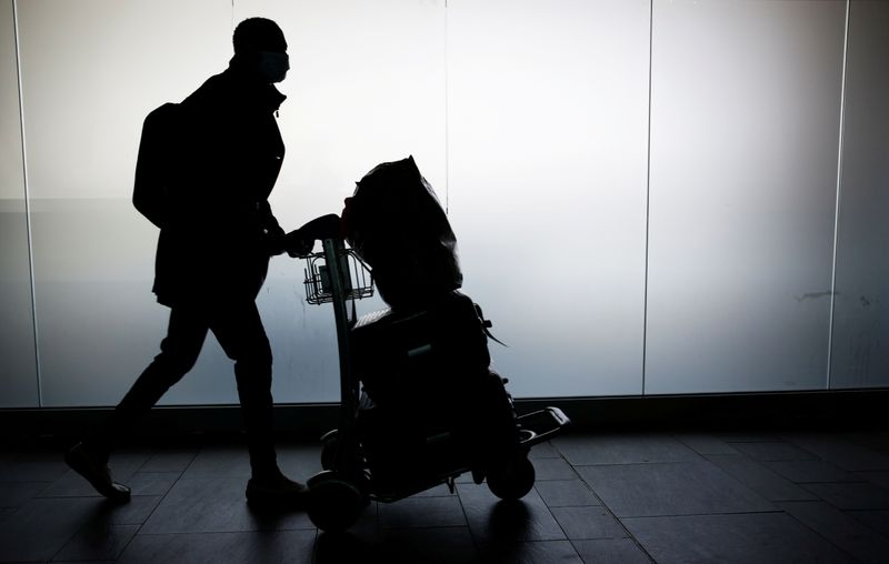 FILE PHOTO: A man walks with his luggage at Fiumicino Airport near Rome
