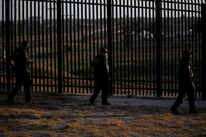 U.S. Border Patrol officers walk along the perimeter fence near the International Bridge between Mexico and the U.S., where migrants seeking asylum in the U.S. are waiting to be processed, in Del Rio