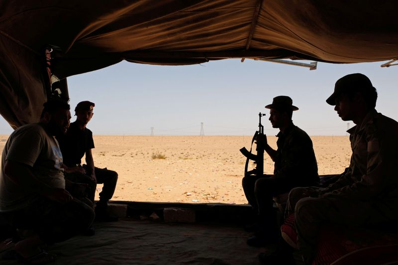 Members of the Libyan National Army (LNA) commanded by Khalifa Haftar sit inside a tent at one their sites in west of Sirte