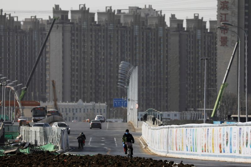 FILE PHOTO: Man rides a bicycle next to a construction site near residential buildings in Beijing