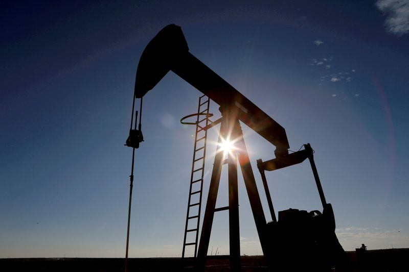 FILE PHOTO: The sun is seen behind a crude oil pump jack in the Permian Basin in Texas