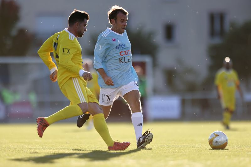 French President Macron plays in a charity soccer match in Poissy